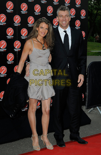 ANNABEL CROFT & husband MEL COLEMAN.At the Sport Industry Awards, Battersea Evolution, London, England, UK, .May 13th 2010..arrivals full length black tie suit grey gray beige dress married couple gathered ruched shoes tanned  wife .CAP/CAN.©Can Nguyen/Capital Pictures.