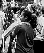 A young girl holds the American flag at Dupont Circle before joining protersters in a May Day March in Washington, DC, USA 01 May 2017. Labor Day or May Day is observed all over the world on the first day of the May to celebrate the economic and social achievements of workers and fight for laborers rights.