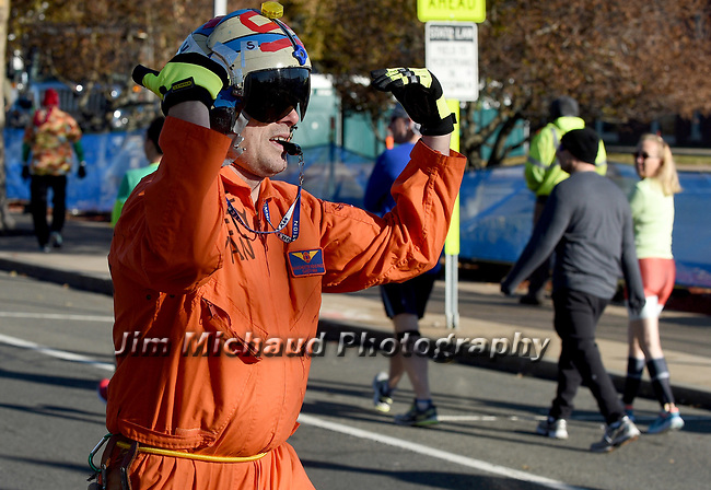 Safety man directs people the start / finish line, prior  to the 81st running of the Manchester Road Race, Thursday, November 23, 2017, in  Manchester. (Jim Michaud / Journal Inquirer)