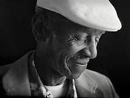 African-american blues musician, John Dee Holeman, poses in low light wearing a hat and a smile