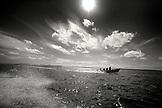 MEXICO, Baja, Magdalena Bay, Pacific Ocean, a small boat cruising through Magdalena Bay