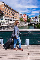 Tourist with suitcase on holiday in Ljubljana, with the Franciscan Church of the Annunciation behind, Slovenia, Europe