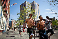 Boys run on a sidewalk in downtown Jersey City during the Spring arrival in New Jersey, United States. 04/16/2012.  Photo by Eduardo Munoz Alvarez / VIEWpress.