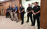 Police officers wait just outside council chambers during the Charlottesville City Council meeting Monday night in Charlottesville, Va. Photo/Andrew Shurtleff