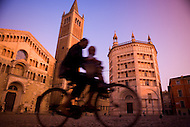A Mother rides with her toddler son in front of the famous Parma Clocktower.