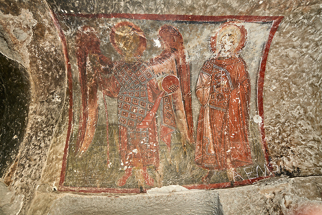 "Pictures & images of Koc Church frescoes, 10th century,  the Vadisi Monastery Valley, ""Manastır Vadisi"",  of the Ihlara Valley, Guzelyurt , Aksaray Province, Turkey.<br /> <br /> The frescoes of Koc church depict two standing figures. One of them is an angel with a staff and a globe in eah hand. The other figure is a saint with an aura around the head. Both are richly clothed with ornaments decorated with pearls."