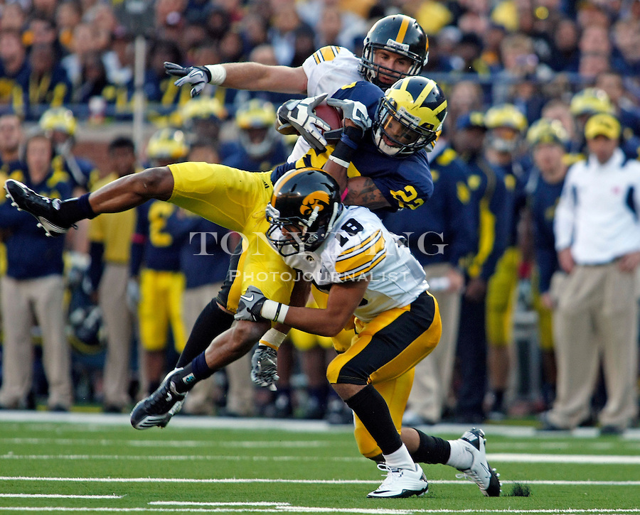 Michigan wide receiver Darryl Stonum (22) catches a 17-yard pass, double teamed by Iowa defensive back Tyler Sash, top, and cornerback Micah Hyde (18), in the fourth quarter of an NCAA college football game, Saturday, Oct. 16, 2010, in Ann Arbor, Mich. Iowa won 38-28. (AP Photo/Tony Ding)
