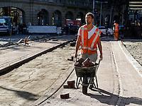 Herinrichting van het Leidseplein in Amsterdam. Stratenmaker met kruiwagen