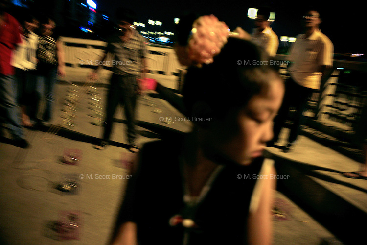 A young girl looks watches a ring-toss game on the roadside in Suzhou, China.