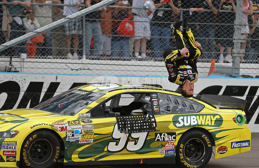Mar. 3, 2013; Avondale, AZ, USA; NASCAR Sprint Cup Series driver Carl Edwards celebrates with a backflip after winning the Subway Fresh Fit 500 at Phoenix International Raceway. Mandatory Credit: Mark J. Rebilas-