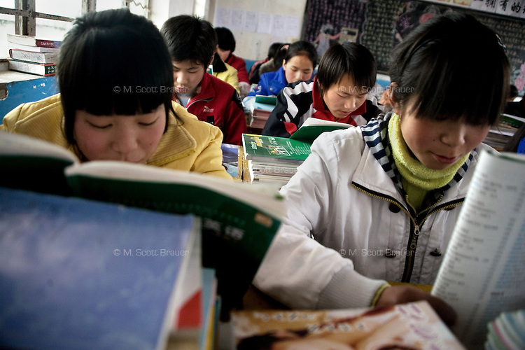 Schoolchildren study in class at Xiaoliji Middle School in Lianshui County, Jiangsu Province, China.  The Pfrang Association, a German charity based in Nanjing, China, sponsors a number of children in the school, providing money for boarding, food, clothing, school supplies, and other necessities to continue schooling.  The majority of children at this school come from poor farming families in rural Jiangsu Province, China.