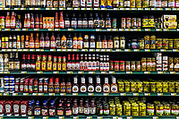 Condiment brands displayed on the shelves of a grocery store.