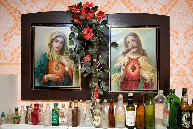 Deronje, Vojvodina, Serbien, 06.05.2007: Eine leere Flaschensammlung unter Gemaelden von Heiligen.<br /> Deronje, Vojvodina, Serbien, 06.05.2007: An empty bottle collection under pictures of saints.<br /><br />[ CREDIT: www.throughmyeyes.de - Merlin Nadj-Torma - phone +49-177-8279119 - merlin@throughmyeyes.de ]