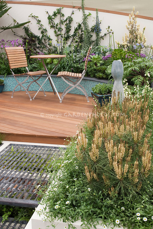 Plantings under the steps of grillwork to a circular wooden deck, raised beds, wall plantings, low-growing pine tree, containers, sculpture, patio furniture, flowers, shrubs, perennials