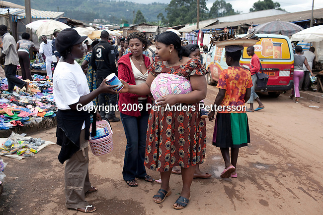 BAMENDA, CAMEROON - AUGUST 8: Patience, age 22, walks in the central market selling the Oldenberger milk powder on August 8, 2009 in Bamenda, Cameroon. It is new on the market and not to easy to convince customers to buy it, as it is more expensive than some other brands on the market. Many small farmers in the area are struggling to cope with low milk prices, expensive inputs and competing with low priced milk powder, that is heavily subsidized by European governments and dumped on international markets such as in Africa. The German company Oldenburger has just started selling powder milk and long life milk on the country. (Photo by Per-Anders Pettersson).....