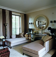 The living room is furnished with a pair of chaise-longues upholstered in silk and a pair of 1940's nickel wall lights either side of a large convex mirror