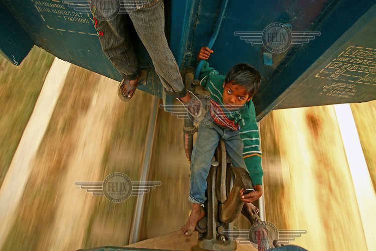 Two boys travel on the locking system of a train carriage to avoid paying the Tk 5 fare (1 USD = 72 Taka). For kids sleeping rough in Dhaka's railway station, travelling on the trains is a fun way to pass some time...