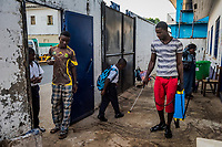 MONROVIA, LIBERIA - FEBRUARY 20: Humphrey, a caretaker, sprays the grounds with a concentrated chlorine solution, prior to the start of morning assembly on the fifth day of school, since schools were closed due to the Ebola outbreak, at the C.D.B. King Elementary School on February 20, 2015 in Monrovia, Liberia. Though Ebola cases have receded into the single digits in Liberia, lingering fear and a depressed economy have dampened the turnout at schools. Many have yet to reopen, having failed to meet the minimum requirements put in place to prevent the transmission of the virus. Many of those that have reopened &ndash; like C.D.B. King, which, though located in the center of the capital, lacks electricity and running water, and has only a few toilet stalls for a student population that numbered 1,000 before Ebola &mdash; are struggling.<br /> Daniel Berehulak for The New York Times