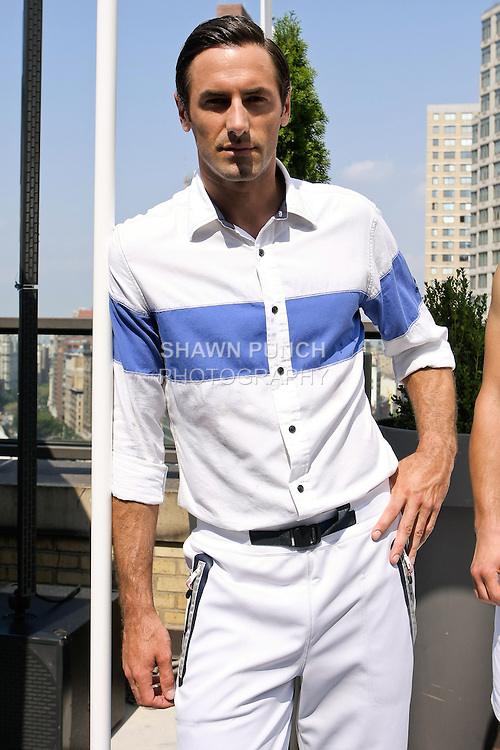 Josh Wald poses in a white/blue colorblock cotton shirt, and bright white cotton/nylon pant from the Nautica Men's Spring 2013 collection by Chris Cox, during New York Fashion Week Spring 2013, September 7, 2012.