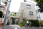 "June 21, 2012, Tokyo, Japan - A woman on her bicycle rides past the ""Yotsuya Tenera"" apartment building complex in a residential area part of Tokyo. This Yotsuya Tenera building has been awarded for its distinct architecture based on its livability and design by the Royal Institute of British Architects (RIBA) on June 21, 2012. This three-story apartment complex located in a residential neighborhood in Tokyo highlights 12 unique types of accessible entrances into the building from two naturally lit and ventilated staircases eliminating the need for corridors. (Photo by Christopher Jue/AFLO)"