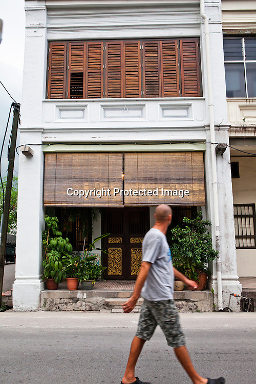 A pedestrian walks past the restored heritage houses in the UNESCO heritage town - Georgetown of Penang, Malaysia. Photo: Sanjit Das/Panos