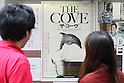July 3, 2010 - Tokyo, Japan - People look at a poster of the Oscar-winning dolphin hunting documentary 'The Cove' near cinema running the movie in Tokyo, Japan, on July 3, 2010. Despite pressure from groups who say the film is anti-Japanese, 'The Cove' will be shown at six theaters in Tokyo and five other Japanese cities beginning Saturday, followed by Nagoya Cinematheque and 15 other theaters across Japan from Aug. 14.