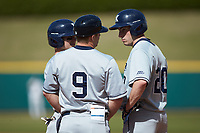 Xavier Musketeers first base coach Kyle Sprague (9) talks to Blaine Griffiths (20) and Nate Soria (5) during the game against the Penn State Nittany Lions at Coleman Field at the USA Baseball National Training Center on February 25, 2017 in Cary, North Carolina. The Musketeers defeated the Nittany Lions 10-4 in game one of a double header. (Brian Westerholt/Four Seam Images)