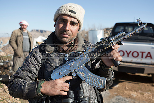 11/12/2014. Sinjar Mountains, Iraq. A Yazidi member of the Iraqi-Kurdish peshmerga shows off his rifle, scrubbed to remove any sign of bluing, at a peshmerga base on the top of Mount Sinjar.<br /> <br /> Although a well publicised exodus of Yazidi refugees took place from Mount Sinjar in August 2014 many still remain on top of the 75 km long ridge-line, with estimates varying from 2000-8000 people, after a corridor kept open by Syrian-Kurdish YPG fighters collapsed during an Islamic State offensive. The mountain is now surrounded on all sides with winter closing in, the only chance of escape or supply being by Iraqi Air Force helicopters.