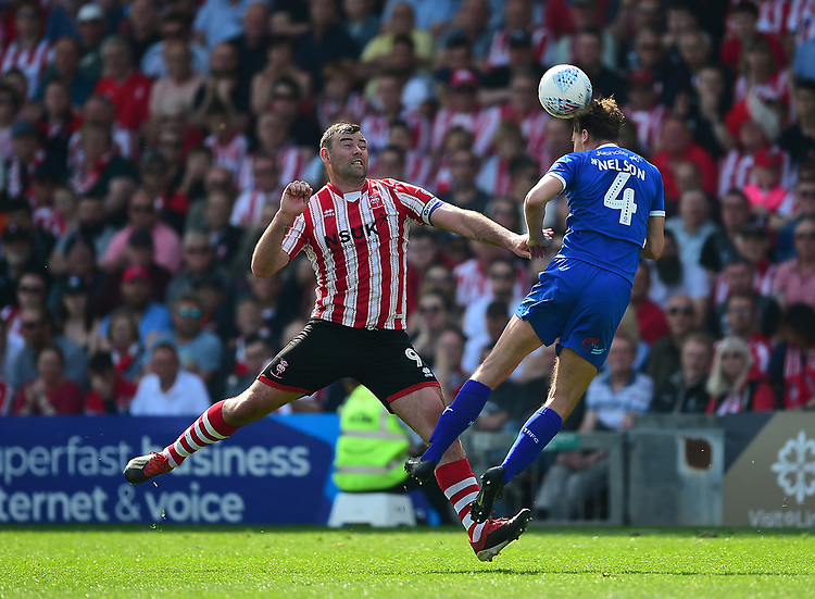 Tranmere Rovers' Sid Nelson clears under pressure from  Lincoln City's Matt Rhead<br /> <br /> Photographer Andrew Vaughan/CameraSport<br /> <br /> The EFL Sky Bet League Two - Lincoln City v Tranmere Rovers - Monday 22nd April 2019 - Sincil Bank - Lincoln<br /> <br /> World Copyright © 2019 CameraSport. All rights reserved. 43 Linden Ave. Countesthorpe. Leicester. England. LE8 5PG - Tel: +44 (0) 116 277 4147 - admin@camerasport.com - www.camerasport.com