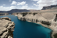 The Band e Amir lakes between Bamiyan and Yakawlang. Hazarajat, Afghanistan..The five lakes of Band-e Amir are Afghanistan's greatest natural wonder. They lie at nearly 3000m in the Koh-e Baba range of the Hindu Kush. Each lake is surrounded by a high retaining wall formed by limestone deposits. This unnatural appearance is explained locally by the miraculous intervention of the Caliph Ali, who raised the walls to dam a dangerous river and bring about the conversion to Islam of the local pagan king. The high mineral content of the water means that the lakes change their hue according to the light and time of day..
