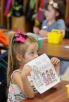 NWA Democrat-Gazette/DAVID GOTTSCHALK  Emily Herrin, a kindergarten student at Owl Creek School, shows her art work to her teacher Beth Dickinson during the first day of school at the  continuous learning school Tuesday, August 4, 2015 in Fayetteville. Schools on the traditional learning calendar will begin Monday, August 17.