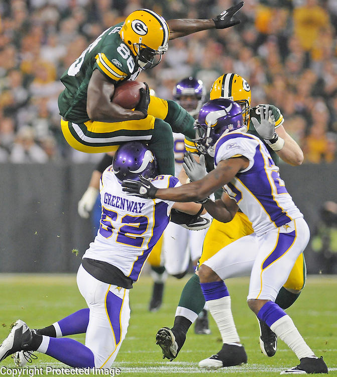 Green Bay Packers tight end Donald Lee goes high over linebacker Chad Greenway for yardage during the first quarter of the game at Lambeau Field in Green Bay, Wis., on Oct. 24, 2010.