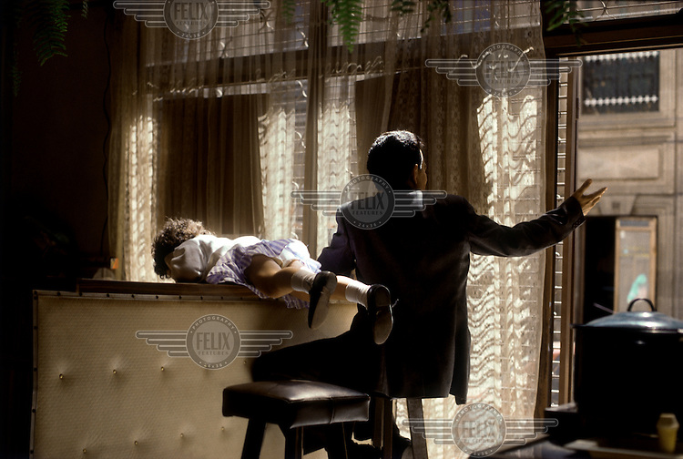 A young girl plays on the counter while her father relaxes at a bar in Huehuetenango.