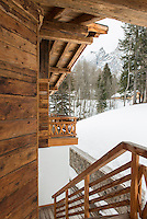 Exterior of the wooden chalet looking from the top of the staircase to the distant mountains