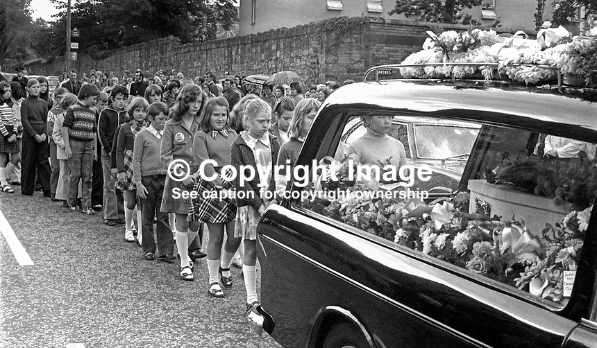 Children follow the hearse containing the little white coffin 3 year old Michelle O'Connor, who died when a UDA/UFF booby trap bomb exploded when she was getting into the family car along with her father, John O'Connor, who received very serious injuries but survived. Michelle was being taken to nursery school. The incident took place on 13th June 1975. The funeral on 16th June 1975 was from the Holy Rosary Church on the Ormeau Road, Belfast, and was attended by hundreds of Protestants as well as Roman Catholics. No reason could be found for the attack other than sectarianism. 197506160497b<br />