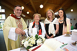 Fr. Denis McNelis lights a candle at the mass in the Star of the Sea Church, Mornington to celebrate the 25th anniversary of his ordination. He is watched by his mother, Bernadette McNelis, sister Breda and niece Rebecca. Photo: Andy Spearman. www.newsfile.ie