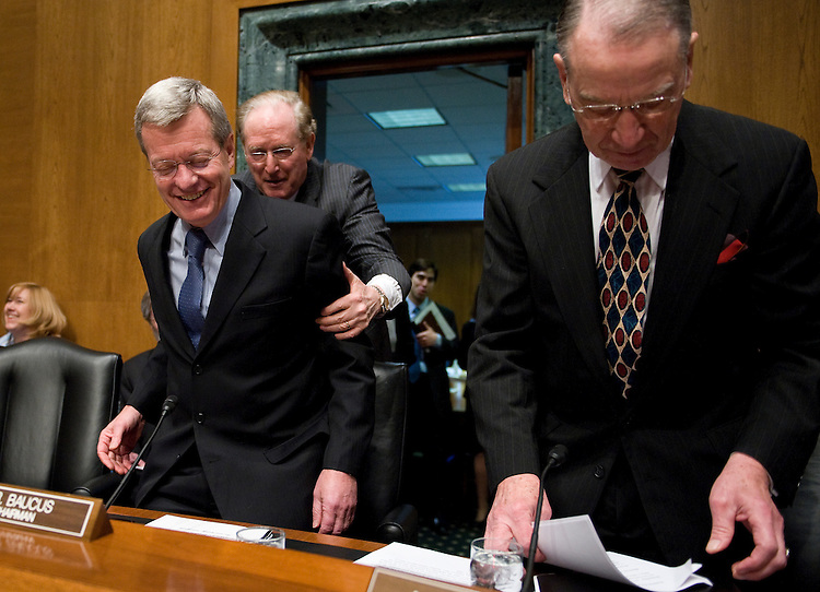 John D. Rockefeller, D-WV., helps a surprised Senator Max Baucus, D-MT., into his seat while Chuck Grassley, R-IA., looks on during a short ceremony at the start of our Finance Committee hearing to honor the Chairman for 30 years on the Finance Committee. Only seven other Senators in history have served longer.