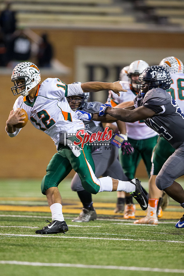 Chazz Surratt (12) of the East Lincoln Mustangs runs away from the pursuit of Lexroy Brown (24) of the Washington Pam Pack during second half action in the NCHSAA 2AA State Championship game at BB&T Field on December 13, 2014, in Winston-Salem, North Carolina.  The Mustangs defeated the Pam Pack 14-13.  (Brian Westerholt/Sports On Film)