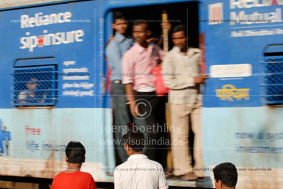 India Mumbai , commuter in city train of western railways, advertisement for Reliance insurance / Indien Bombay , S-Bahn Zuege befoerdern taeglich Millionen von Pendlern zwischen Zentrum und Suburbans , Werbung fuer Versicherung der Firma Reliance