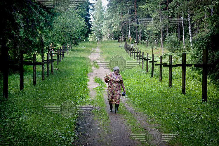 Valentina Ivachko walks along a path lined with wooden crosses to commemorate the victims of Stalin's purges, murdered and buried at Kurapaty.