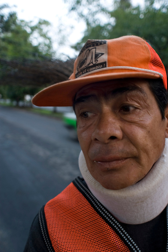 Ricardo Herrejon Vargas sweeps the streets at dawn of the wealthy Mexico City neighbourhood; Las Lomas.  He wears a neckbrace from an injury he suffered years ago unrelated to his work.  He smokes over 2 packs a day. Mexico City 09-08-07