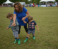 NWA Democrat-Gazette/ANDY SHUPE<br /> Roberta Reuter of Huntley, Ill., leads her grandsons Aston Reuter, 4, (left) and Pierce Reuter, 3, both of Fayetteville, in the traditional Stomping of the Divots during halftime Saturday, Sept. 8, 2018, during the 29th annual Polo in the Ozarks at the Buell Farm in Goshen. This event features a polo match, games, vendors, music and food to benefit Life Styles Inc.