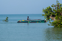 Africa, Madagascar, Ankilibe. Bakuba Hotel. Near the Tropic of Capricorn on the Mozambique channel. Man in wooden canoe.