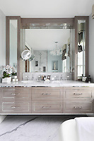 Luxury fittings of marble flooring, splashbacks and marble tops combined with polished wood cabinetry in the ensuite bathroom