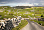Country lane and dry stonewalls, Malham, Yorkshire Dales national park, England, UK