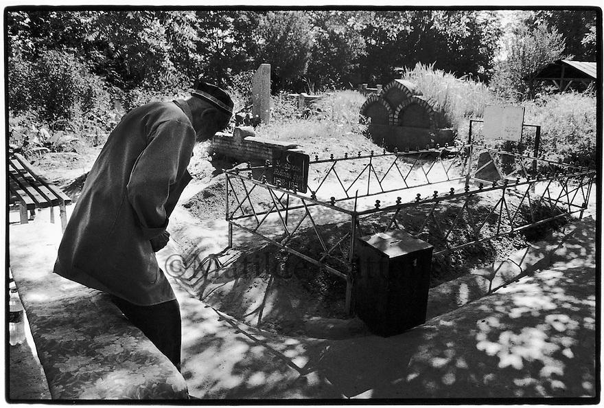 Uzbekistan - Tashkent - Prayer at Zengi Ata cemetery, one of the few that includes Orthodox and Muslim graves.