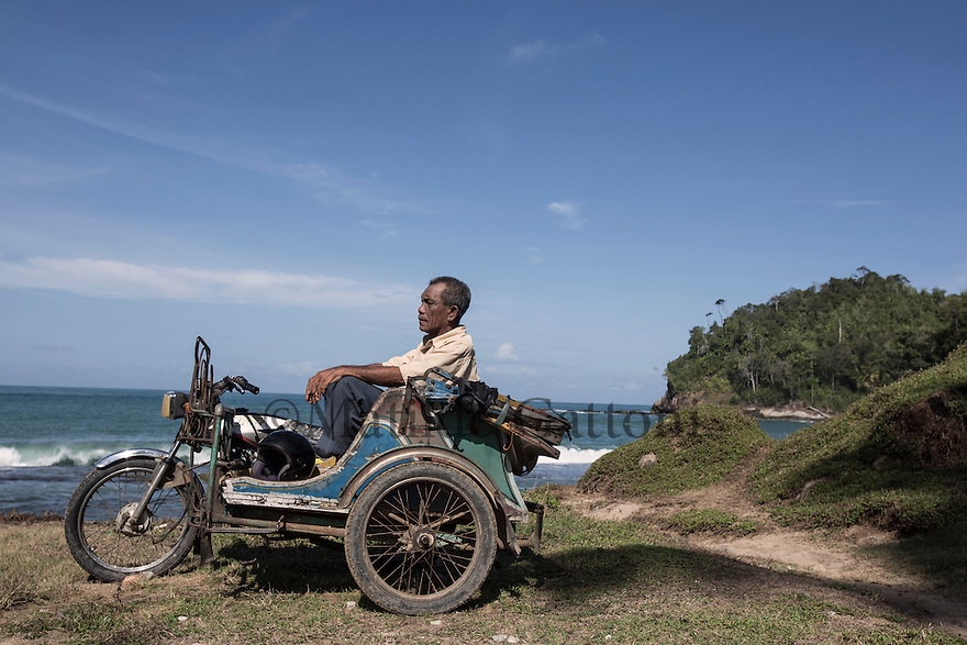 "Indonesia – Sumatra – Aceh – Calang – Kamisari, 59-year-old taxi driver.  Kamisari lost his wife, two sons and three sisters-in-law in the tsunami, escaping death by the skin of his teeth. The water hit him while he was renovating the village mosque, bringing him into open sea. There, the man swam for hours, in the vain attempt to reach the coastline. The first aid and ration foods arrived only four days later, forcing more than 400 survivors to feed on fruits and coconuts for more than 36 hours. Few days after the tsunami, one of Kamisari's sons announced him his death by visiting him in his dream. The bodies of his previous family members were never retrieved. ""I think about them when I go to the sea. I think they are buried there"" he says with a peaceful and resigned smile."