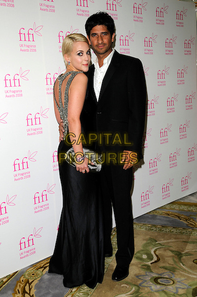 MIRANDA RAISON & RAZA JAFFREY.The FIFI UK Fragrance Awards 2008 at the Dorchester Hotel, Park Lane, London, England..April 23rd 2008.full length black dress suit looking over shoulder grey gray clutch bag purse .CAP/CAN.©Can Nguyen/Capital Pictures.
