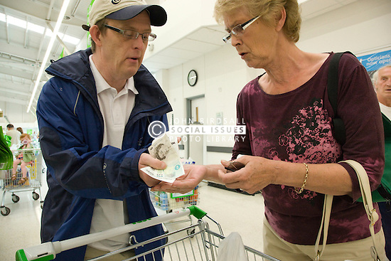 Day Service Officer helping to check the day service user with learning disability's money at the supermarket check out,