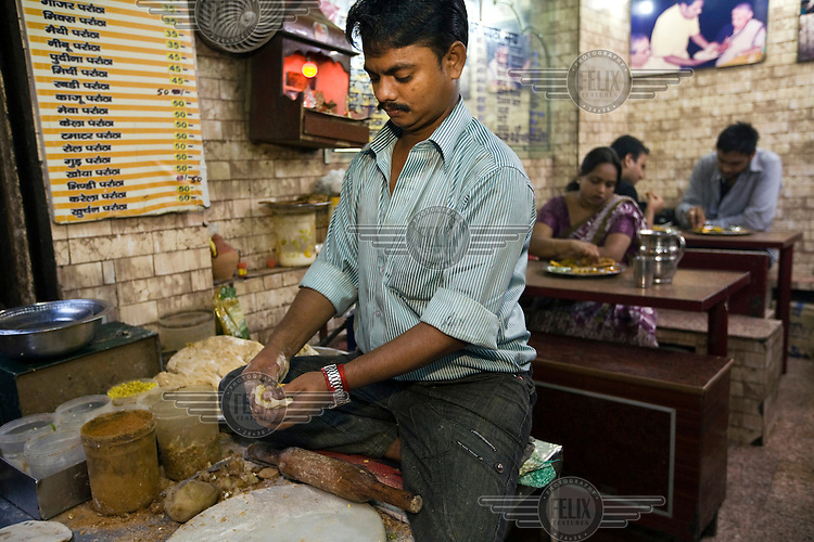 Ram Billas making paratha at Parawthe Wala restaurant in Old Delhi. The parantha is an Indian fried bread, folded and filled with fillings and then fried.